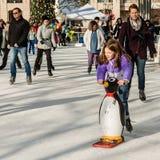 Meisjesschaatsen met Assist van Toy Penguin royalty-vrije stock fotografie