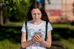 Meisjesschoolmeisje De zomer in aard In zijn handen houdt een smartphone Schrijft een bericht op Internet Het concept van royalty-vrije stock foto