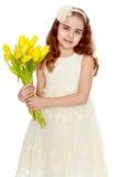 Meisjesschoolmeisje met een boeket van tulpen stock fotografie