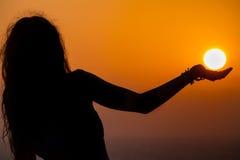 Meisjessilhouet, haar palm die de zon schijnen te steunen zoals Stock Foto