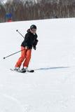 Meisjesskiër die onderaan de ski uit een berg op een zonnige dag komen stock foto's