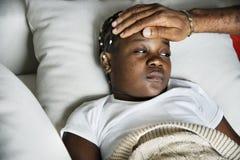 Meisjesslaap met ziekte op het bed stock fotografie