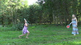 Meisjesspel met het zwangere badminton van het moedertennis in groen park stock footage