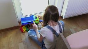 Meisjesspelen met stuk speelgoed auto en stuk speelgoed bakstenen stock video