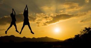 Meisjessprong op de hemel onder zonsonderganglicht Stock Fotografie
