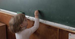 Meisjestekening bij bord die een krijt in klaslokaal gebruiken Onderwijsproces stock videobeelden