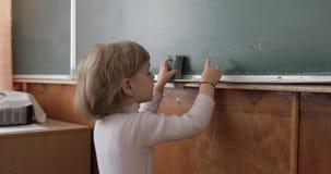 Meisjestekening bij bord die een krijt in klaslokaal gebruiken Onderwijsproces stock footage