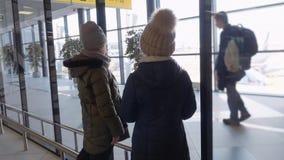 Meisjestiener die aan luchthavenvenster kijken terwijl het wachten van vliegtuigen in vertrekzitkamer Jong meisje die aan vliegtu stock video