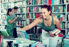 Meisjestiener die boek in winkel kiezen royalty-vrije stock foto's