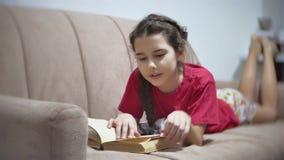 Meisjestiener die een boek lezen die op bank binnen liggen meisjesjong geitje die een boek lezen die op een binnen bank liggen stock footage