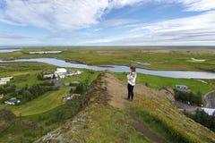 Meisjestiener die het landschap van Kirkjubaejarklaustur-dorp en de stroom van Skafta-rivier in Skaftarhreppur-gemeente registrer royalty-vrije stock afbeelding