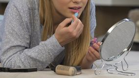 Meisjestiener die make-up met goedkope lipgloss, cosmetischee producten beneden de maat doen stock videobeelden