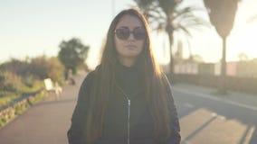 Meisjestoerist met een rugzak op haar achtergangen langs de palmpromenade stock videobeelden