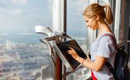 Meisjestoerist met monitor van computer bij venster van wolkenkrabber stock foto