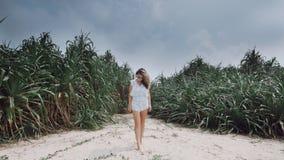 Meisjestribunes tegen de achtergrond van uitheemse gewassen op het strand Stock Foto