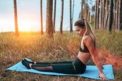 Meisjesturner, mooie vrouw die oefeningen in het de zomerpark doen, die op een deken in hout zitten Lange haar gelooide huid stock foto's