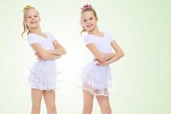 2 meisjesturner in witte kostuums Stock Foto's