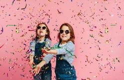 Meisjestweelingen die met confettien spelen royalty-vrije stock afbeeldingen