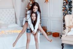 Meisjestweelingen voor de spar Nieuwjaar` s Vooravond Kerstmis Comfortabele vakantie bij de spar met lichten royalty-vrije stock afbeeldingen