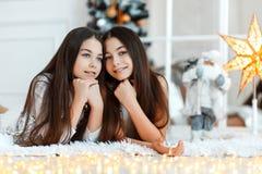Meisjestweelingen voor de spar Nieuwjaar` s Vooravond Kerstmis Comfortabele vakantie bij de spar met lichten stock afbeelding