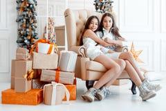 Meisjestweelingen voor de spar Nieuwjaar` s Vooravond Kerstmis Comfortabele vakantie bij de spar met lichten royalty-vrije stock fotografie