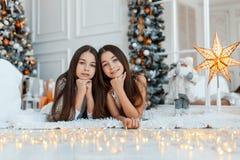 Meisjestweelingen voor de spar Nieuwjaar` s Vooravond Kerstmis Comfortabele vakantie bij de spar met lichten royalty-vrije stock foto's