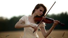 Meisjesviolist die de viool op tarwegebied spelen stock footage