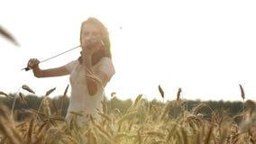Meisjesviolist die de viool op tarwegebied spelen stock videobeelden