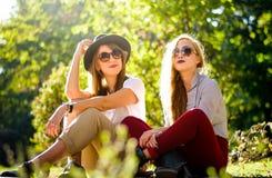 Meisjesvrienden die de herfst van dag in het park genieten royalty-vrije stock foto