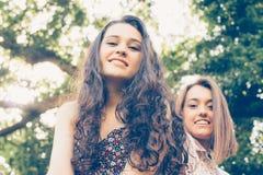 Meisjesvrienden die op een boomstam zitten Royalty-vrije Stock Afbeeldingen