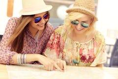 Meisjesvrienden die op kaart controleren Stock Foto's