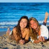 Meisjesvrienden die pret het gelukkige liggen op het strand hebben Stock Foto