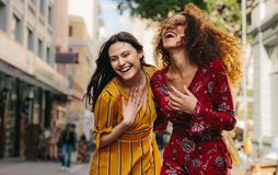 Meisjesvrienden die pret op stadsstraat hebben royalty-vrije stock afbeelding