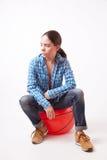Meisjesvrouw die in een blauw overhemd en jeans op de bal zitten Stock Foto's