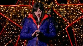 Meisjesvrouw die slimme telefoon houden bekijkend sociale media de nacht achter het licht van de bokehwinter stock videobeelden