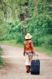 meisjesvrouw in leerjasje, blauwe denimborrels, strohoed, het bevindende lopen op landweg wild bos met reiszak Stock Foto's