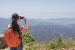 Meisjeswandelaar met rugzak die zich bovenop de berg bevinden en een beeld van vallei nemen Royalty-vrije Stock Foto's