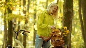 Meisjeswapens die oud fietsstuur met bloemenmand houden De vrouw van de herfst Mooie vrouw die in het bos op een dalingsdag loopt stock video