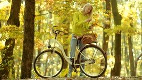 Meisjeswapens die oud fietsstuur met bloemenmand houden Mooie jonge vrouw op fiets in park Onbezorgde vrouw De herfst stock videobeelden