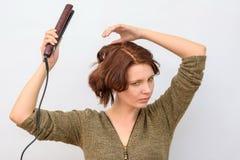 Meisjeswind het haar op de haarkrulspelden stock afbeeldingen
