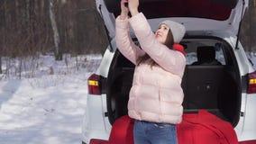 Meisjeszitting in auto op zonnige de winterdag, die voor de camera stellen die zoet glimlachen stock videobeelden