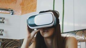 Meisjeszitting in badkamers met virtueel werkelijkheidsmasker op hoofd Rond het kijken stock videobeelden