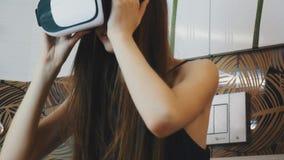 Meisjeszitting in badkamers in virtuele werkelijkheidsglazen op hoofd Rond het kijken stock video
