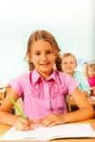 Meisjeszitting bij bureau in klaslokaal en het schrijven Stock Fotografie