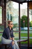 Meisjeszitting bij de bushalte Stock Foto