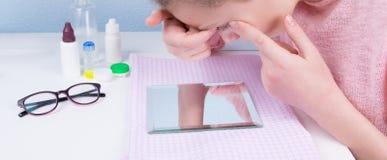 meisjeszitting bij de lijst die, die in de spiegel kijken en contactlenzen dragen om visie te verbeteren stock afbeeldingen