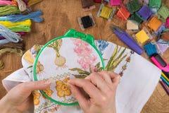 Meisjeszitting bij een lijst waar alles noodzakelijk voor borduurwerk, een groter beeld borduurt royalty-vrije stock foto