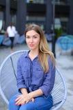Meisjeszitting bij koffie die buiten en blauw overhemd dragen Royalty-vrije Stock Fotografie