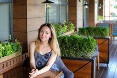 Meisjeszitting bij koffie en het rusten dichtbij ruimteinstallaties Royalty-vrije Stock Foto's