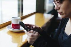 Meisjeszitting bij koffie gebruikend tablet en drinkend een thee royalty-vrije stock afbeeldingen